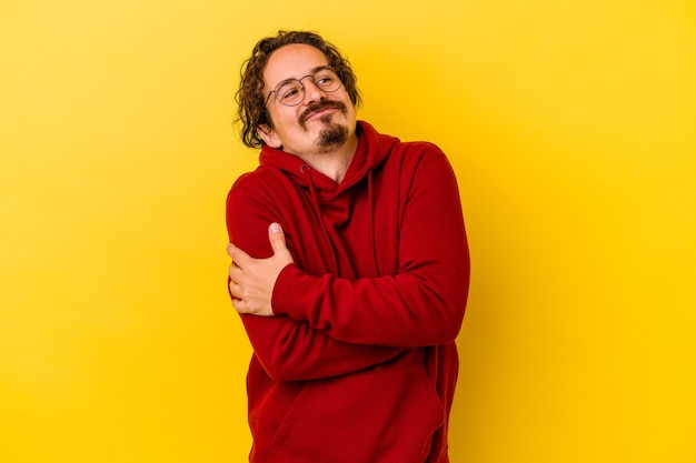 Young caucasian man isolated on yellow wall hugs, smiling carefree and happy