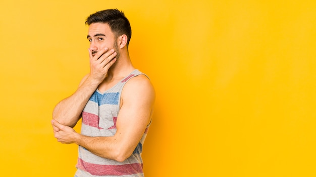 Young caucasian man isolated on yellow wall scared and afraid.