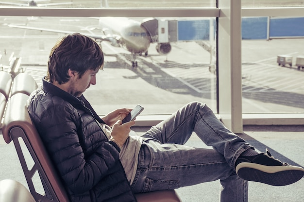 Young caucasian man in jeans and outerwear is sitting in chair airport waiting hall and using smartphone.