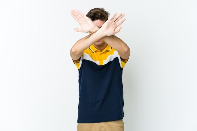 Молодой кавказский человек держит скрещенными руками, концепцию отрицания.
