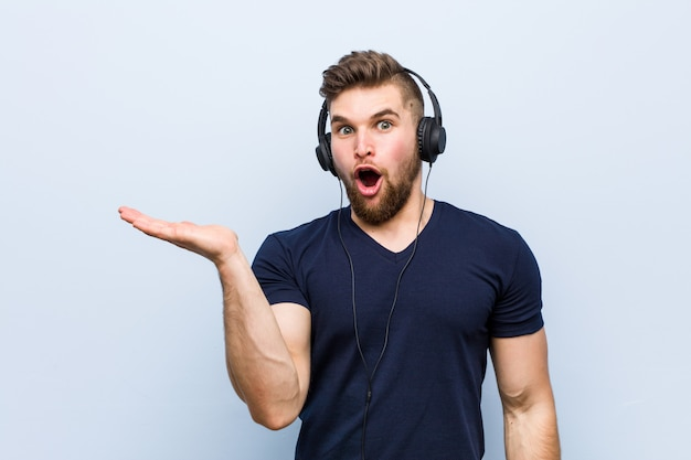 Young caucasian man listening to music impressed holding copy space on palm.