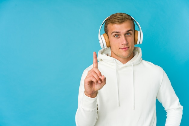 Young caucasian man listening music isolated on blue,  showing number one with finger.