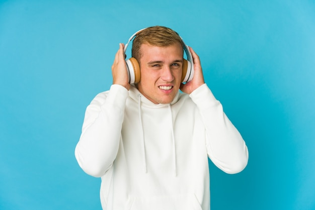 Young caucasian man listening music isolated on blue space covering ears with hands.