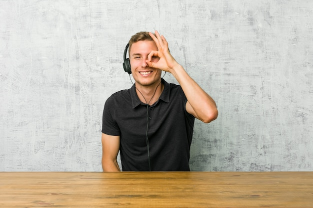 Young caucasian man listening to music with headphones excited keeping ok gesture on eye.