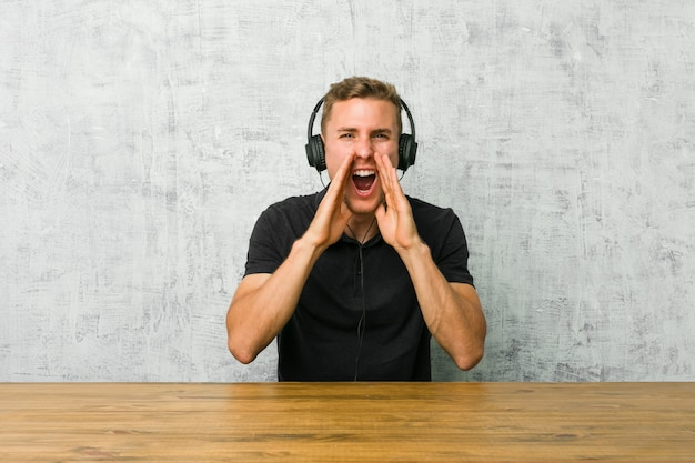 Young caucasian man listening to music with headphones shouting excited to front.