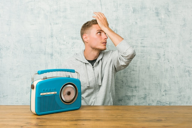 Young caucasian man listening to the radio forgetting something, slapping forehead with palm and closing eyes.