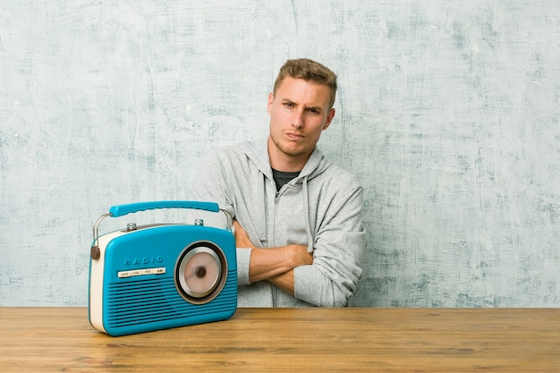 Young caucasian man listening to the radio frowning face in displeasure, keeps arms folded.