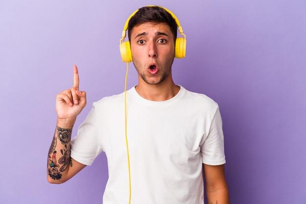 いくつかの素晴らしいアイデア、創造性の概念を持っている紫色の背景に分離された音楽を聞いている若い白人男性。
