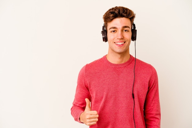 Молодой кавказский человек слушает музыку на белом фоне, улыбаясь и поднимая палец вверх