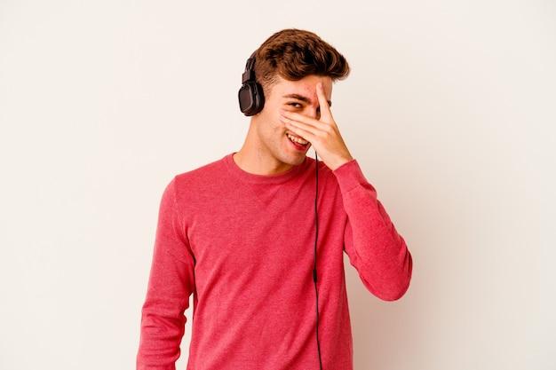 白い壁に隔離された音楽を聴いている若い白人男性が指で正面を点滅し、恥ずかしい顔を覆っている