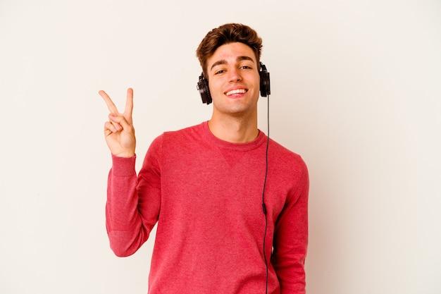 손가락으로 평화의 상징을 보여주는 즐겁고 평온한 흰 벽에 고립 된 음악을 듣고 젊은 백인 남자.