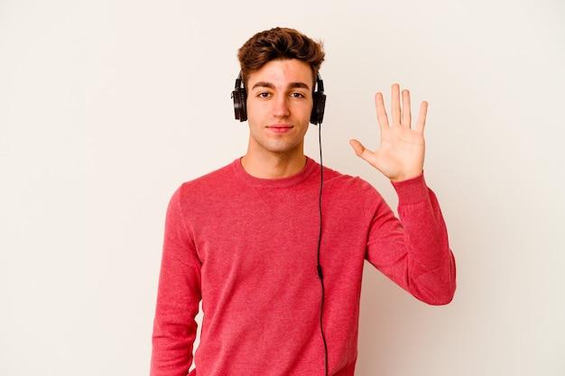 Молодой человек кавказской, слушающий музыку, изолированную на белой стене, улыбается веселый, показывая номер пять с пальцами.
