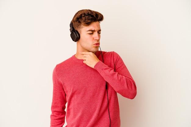 흰 벽에 고립 된 음악을 듣고 젊은 백인 남자는 바이러스 또는 감염으로 인해 목에 통증을 앓고 있습니다.