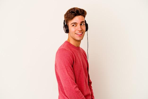 흰색 음악을 듣고 젊은 백인 남자는 옆으로 웃고, 밝고 쾌적한 보인다.