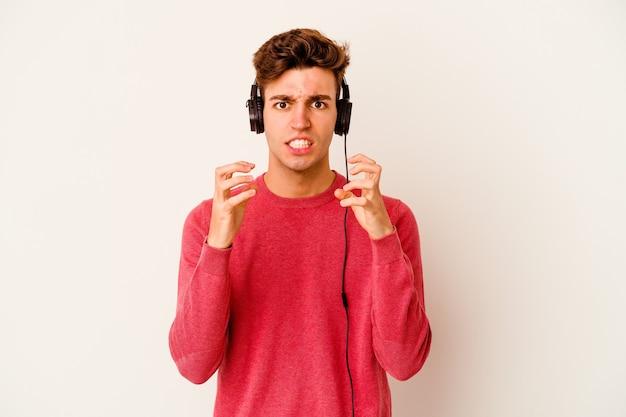 흰색에 음악을 듣고 젊은 백인 남자는 긴장된 손으로 비명 화가.