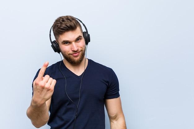 초대하는 것처럼 손가락으로 가리키는 음악을 듣고 젊은 백인 남자가 더 가까이 오십시오.