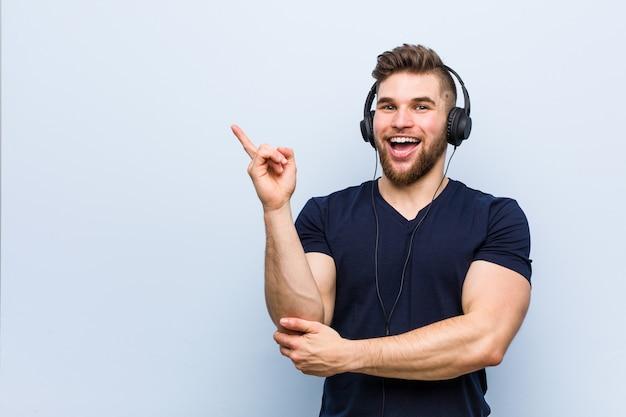 유쾌 하 게 집게 손가락으로 가리키는 웃 고 음악을 듣고 젊은 백인 남자.
