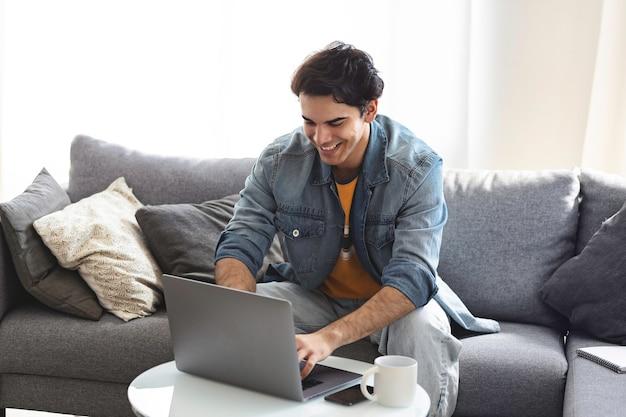 Молодой кавказский мужчина смотрит на экран ноутбука, разговаривает по видеосвязи онлайн или болтает в социальных сетях, сидя на диване у себя дома. концепция технологии