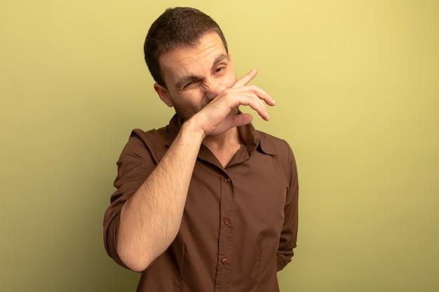 Молодой кавказский мужчина смотрит в камеру, вытирая нос рукой, изолированной на оливково-зеленом фоне с копией пространства