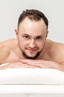 Молодой кавказский человек, лежащий спереди на столе спа, ожидая косметических процедур