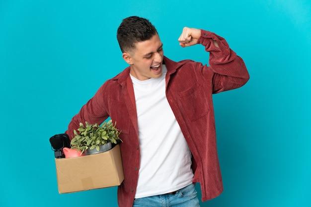 Молодой кавказский мужчина делает движение, поднимая коробку, полную вещей, изолированную на синей стене, празднуя победу