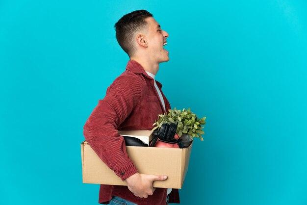 Молодой кавказский мужчина делает движение, поднимая коробку, полную вещей, изолированную на синей стене, смеясь в боковом положении