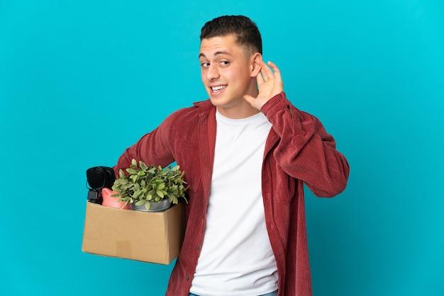 귀에 손을 넣어 뭔가를 듣고 파란색 벽에 고립 된 것들로 가득한 상자를 집어 들고 움직이는 젊은 백인 남자