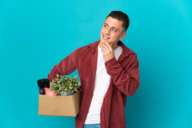 웃는 동안 찾고 파란색 벽에 고립 된 것들의 전체 상자를 따기 동안 이동하는 젊은 백인 남자