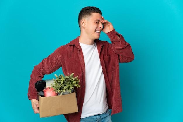 Молодой кавказский мужчина делает движение, поднимая коробку, полную вещей, изолированную на синей стене, много улыбаясь