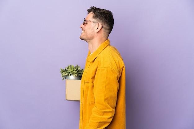 Молодой кавказский мужчина делает движение, поднимая коробку, полную вещей, изолированную на фиолетовом фоне, смеясь в боковом положении