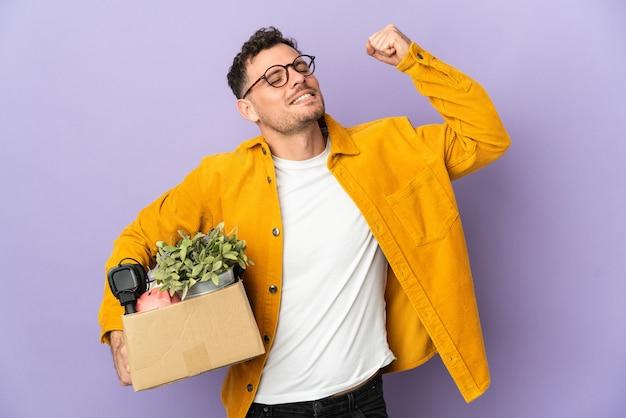 Молодой кавказский мужчина делает движение, поднимая коробку, полную вещей, изолированную на фиолетовой стене, празднуя победу