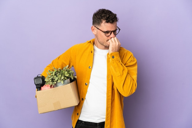 Молодой кавказский мужчина делает движение, поднимая коробку, полную вещей, изолированную на фиолетовой стене, сомневаясь