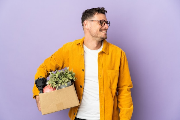 Молодой кавказский мужчина делает движение, поднимая коробку, полную вещей, изолированную на фиолетовой стене, смотрящей в сторону