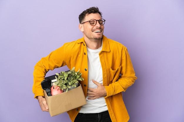 Молодой кавказский мужчина делает движение, поднимая коробку, полную вещей, изолированную на фиолетовой стене, много улыбаясь