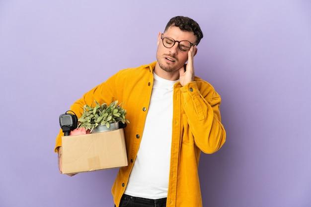 Молодой кавказский мужчина делает движение, поднимая коробку, полную вещей, изолированную на фиолетовом, с головной болью