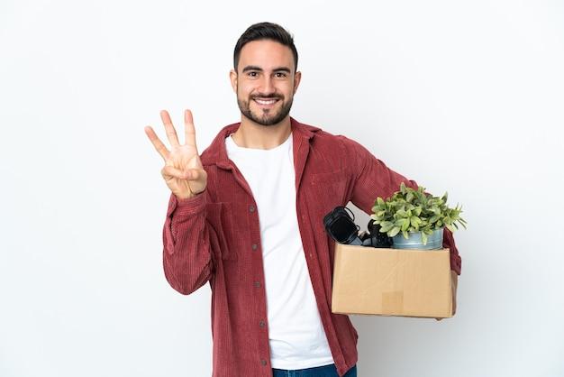 흰색 배경에 행복하고 손가락으로 세 세에 고립 된 것들의 전체 상자를 따기 동안 이동하는 젊은 백인 남자