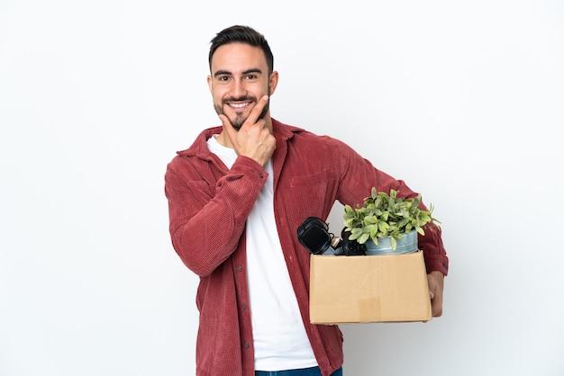 Молодой кавказский человек делает ход, поднимая коробку, полную вещей, изолированную на белом фоне, счастливую и улыбающуюся