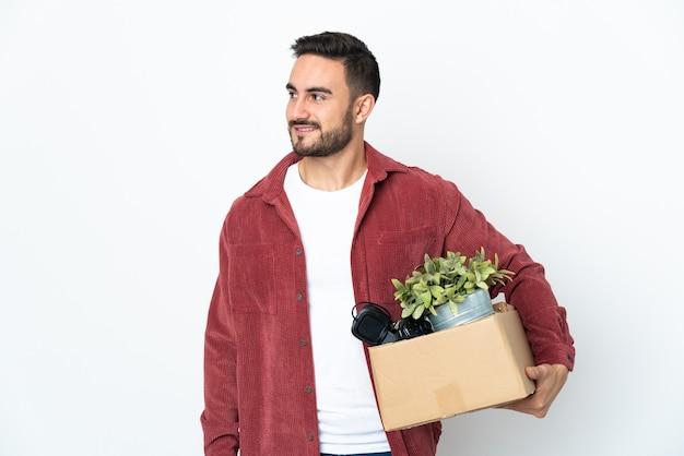 Молодой кавказский мужчина делает движение, поднимая коробку, полную вещей, изолированную на белом фоне, глядя в сторону и улыбаясь
