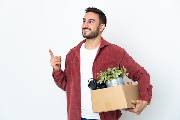 Молодой кавказский мужчина делает ход, поднимая коробку, полную вещей, изолированную на белом фоне, указывая на отличную идею