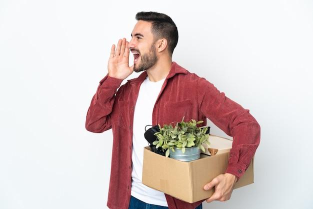 Молодой кавказский мужчина делает движение, поднимая коробку, полную вещей, изолированную на белом фоне, кричит с широко открытым ртом