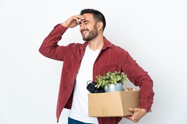 Молодой кавказский человек делает ход, поднимая коробку, полную вещей, изолированную на белом фоне, много улыбаясь