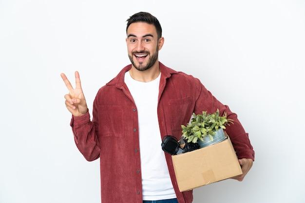 Молодой кавказский человек делает ход, собирая коробку, полную вещей, изолированную на белом фоне, улыбается и показывает знак победы