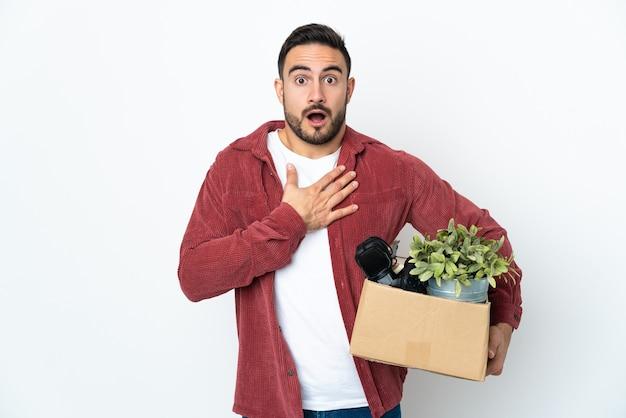 Молодой кавказский мужчина делает ход, поднимая коробку, полную вещей, изолированную на белом фоне, удивлен и шокирован, глядя вправо