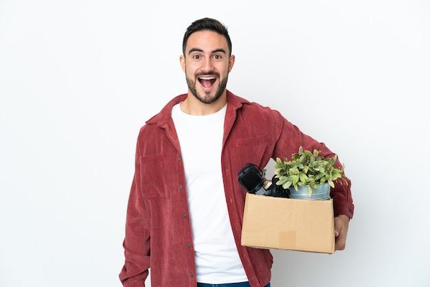 Молодой кавказский мужчина делает движение, поднимая коробку, полную вещей, изолированную на белом фоне с удивленным выражением лица