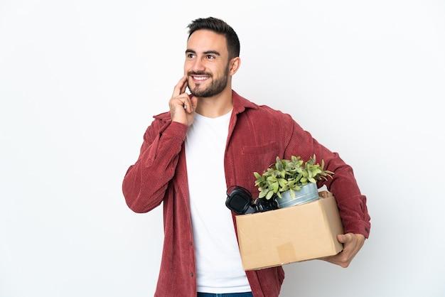 Молодой кавказский мужчина делает движение, поднимая коробку, полную вещей, изолированную на белой поверхности, думая об идее, глядя вверх