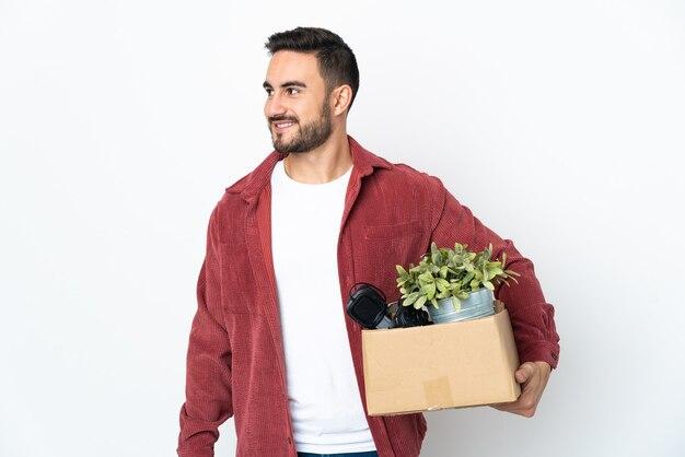 Молодой кавказский человек делает ход, собирая коробку, полную вещей, изолированную на белой стене, смотрящей в сторону