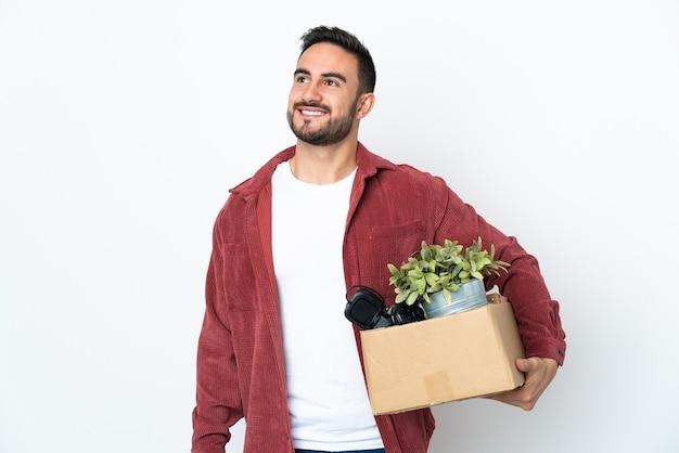 見上げながらアイデアを考えて白い壁に隔離されたものでいっぱいの箱を拾いながら動きをしている若い白人男性