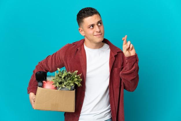 Молодой кавказский мужчина делает движение, поднимая коробку, полную изолированных вещей