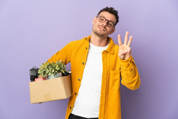 孤立したものでいっぱいの箱を拾いながら動きをしている若い白人男性