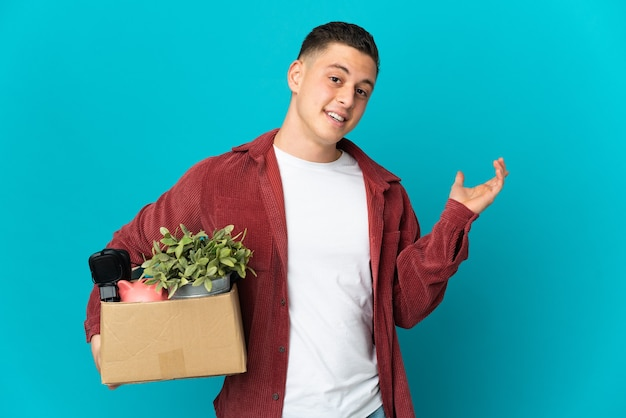 Young caucasian man making a move while picking up a box full of things isolated on blue extending hands to the side for inviting to come
